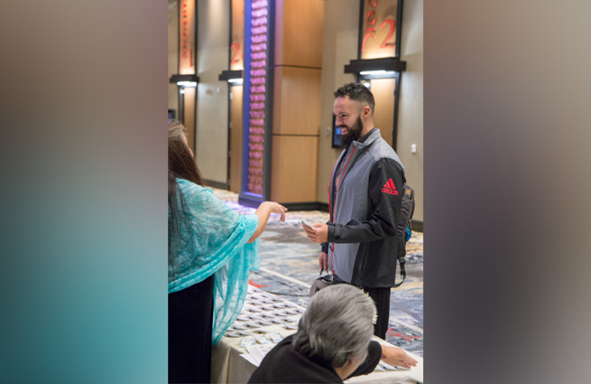 Tulalip Tribes' 2018 Raising Hands photo of MC speaking with a guest.