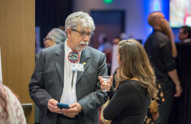 Tulalip Tribes' 2018 Raising Hands photo of volunteer with a file folder speaking with a guest.