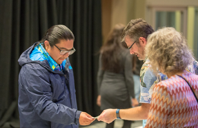 Tulalip Tribes' 2018 Raising Hands photo of volunteer handing a guest with a blue coat a complimentary gift bag.